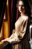 20世纪初替换者米黄葡萄酒礼服的少妇  免版税库存图片