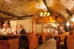 17世纪大厦历史餐馆地下与吃的人的晚餐 免版税库存照片