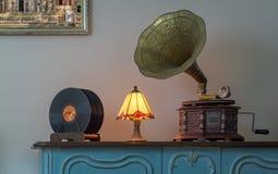 19世纪留声机和唱片在米黄墙壁和垂悬的绘画木桌和背景上  库存照片
