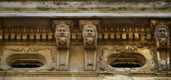 18世纪的老雕塑以人头的形式,在利沃夫州,乌克兰装饰高层建筑物门面  库存照片