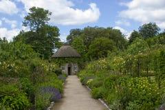 19世纪盖了围绕美丽的花床和石渣道路包围的房子在被围住的庭院里在西部教务长加尔德角 免版税图库摄影