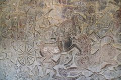 12世纪被雕刻的墙壁,在马背上描述战士在显示损伤的迹象从许多游人接触的吴哥窟  免版税库存照片