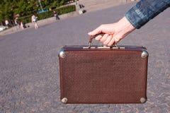 20世纪30年代手提箱的葡萄酒手提箱在妇女手上在backgr 免版税库存照片