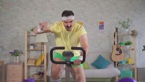 20世纪80年代的滑稽的精力充沛的运动员与髭的订婚锻炼脚踏车并且倾吐从一个瓶的水在他的 股票视频