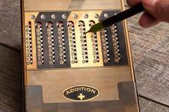 从20世纪30年代的葡萄酒手工计算器与铁笔 库存图片