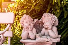 丘比特和天使雕象、男孩和女孩雕象在庭院里 图库摄影