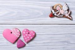 丘比特和桃红色心脏。曲奇饼框架在情人节 免版税库存照片