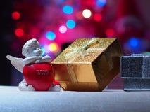 丘比特和礼物盒在bokeh背景  免版税库存图片