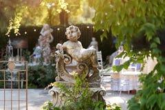 丘比特雕塑在庭院里,逗人喜爱的丘比特雕象在室外餐馆 库存照片