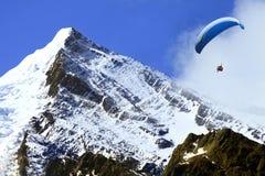 业余爱好横向滑翔伞雪瑞士 免版税图库摄影