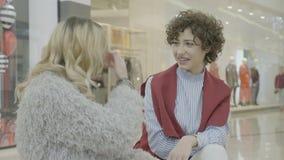 业务经理妇女坐长凳和谈论与她的少年朋友在关于购物预算的购物中心大厅- 影视素材
