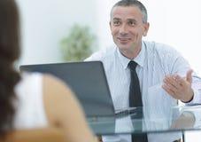业务顾问坐在他的书桌并且与他们的客户协商 免版税图库摄影