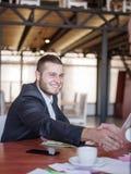 业务顾问,当工作在队时 一个小组年轻工人在一次会议上在公司会议室 库存照片