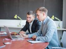 业务顾问,当工作在队时 一个小组年轻工人在一次会议上在公司会议室 免版税库存照片