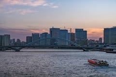 东京地平线、Kachidoki桥梁和船航行在Sumida河 库存照片