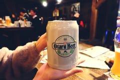东京,日本- December 30, 2017 :妇女在日本递拿着杯子在酒吧的日本啤酒或餐馆 免版税库存照片