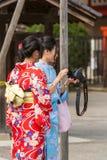 东京,日本- 2017年10月31日:一件和服的两个女孩在城市街道上 垂直 免版税库存图片