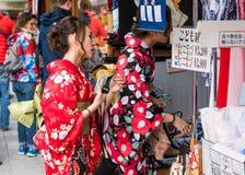 东京,日本- 2017年10月31日:一件和服的两个女孩在城市街道上 特写镜头 免版税图库摄影