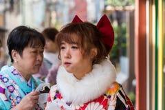东京,日本- 2017年10月31日:一件和服的两名日本妇女在城市街道上 特写镜头 免版税库存图片
