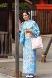 东京,日本- 2017年10月31日:一件蓝色和服的女孩在城市街道上 垂直 免版税图库摄影