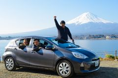 东京,日本- 2015年3月30日:亚裔游人坐有富士山的汽车 库存照片