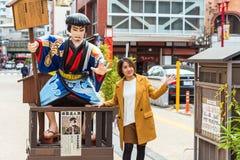东京,日本- 2017年10月31日:在一个雕塑附近的女孩在城市街道上 复制文本的空间 库存图片