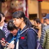 东京,日本- 2017年10月31日:在城市街道上的日本学校女孩 特写镜头 图库摄影