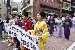 东京,日本- 2017年9月24日:妇女穿戴了与拿着横幅的和服在Shinagawa Shukuba Matsuri节日游行  免版税库存照片