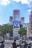 东京,日本- 2018年8月21日:涩谷在涩谷站前面的横穿交叉点在一明亮的天天空蔚蓝 库存图片