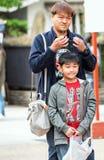 东京,日本- 2017年10月31日:父亲和儿子在城市街道上 垂直 复制文本的空间 免版税库存照片