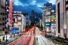 东京,日本- 2016年10月16日:都市风景在晚上在有摩天大楼、快速的交通和人的新宿区在街道上 库存图片