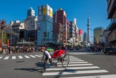东京,日本- 2014年11月, 23日:观光乘人力车的东京 库存照片