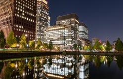东京,日本- 2015年10月6日:东京在水的都市风景在与Buisiness大厦的晚上和Reflectin 图库摄影
