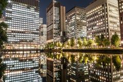 东京,日本- 2015年10月6日:企业大厦和反射在水 与长的曝光的夜照片在东京,日本 免版税库存照片