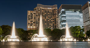 东京,日本- 2015年10月6日:喷泉在与光的晚上 企业大厦在背景中 长的风险照片 图库摄影