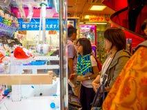 东京,日本2017年6月28日- :看在一台玩具自动贩卖机的未认出的人民被分类的Hello Kitty玩偶在东京 免版税库存图片