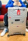 东京,日本10 02 2018有贴纸的明亮的时髦的铝手提箱在时兴地坐在地铁的加工好的年轻人旁边 库存图片