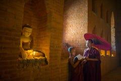 东南亚初学者点燃在Buddihist寺庙里面的蜡烛 免版税库存照片