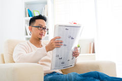 东南亚男性读取新闻纸张 免版税库存图片