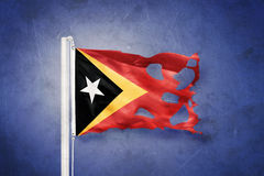 东帝汶飞行被撕毁的旗子反对难看的东西背景的 库存照片