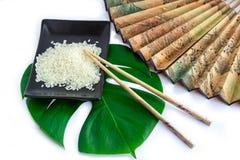 东方人套米、筷子、绿色叶子和transp 免版税库存图片