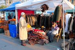 东方地毯和衣物卖主等待在市场上的顾客 库存图片