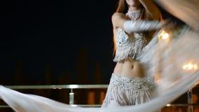 东方民族服装的美丽的少妇在室外的晚上跳舞 影视素材