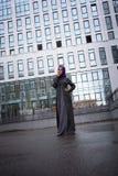 东方礼服的年轻回教妇女在一个现代大厦的背景 库存图片
