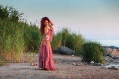 东方舞蹈服装的美丽的少妇由海 免版税库存照片
