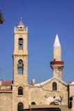 东正教在清真寺尖塔旁边的钟楼,利马索尔,塞浦路斯 免版税库存图片