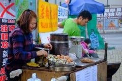 东涌,香港- 2016年11月27日:妇女是被蒸的鸡和销售的鹌鹑蛋作为快餐在冬天期间 库存图片