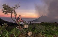 东爪哇省,印度尼西亚2015年6月:Kawah伊真火山休息在树的日落的硫磺矿工在完成他的采矿活动以后 免版税库存图片