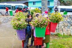 东范,河江市,越南, 2017年12月18日, :未认出的少数族裔哄骗与油菜籽花篮子在Hagiang 库存图片