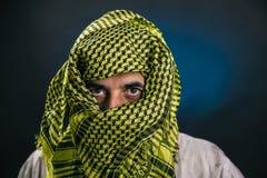 东部出现一件传统全国阿拉伯礼服的一个人用手帕包括他的面孔,离开仅他的眼睛 库存照片
